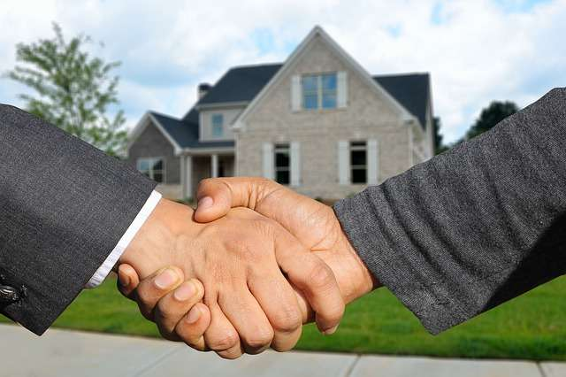 houses for rent property management from Red Hawk as seen in this photo of clients shaking hands